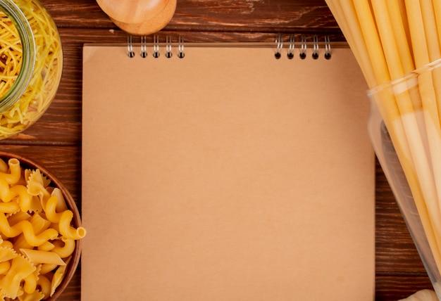 Vista do close-up de diferentes tipos de macarrão em tigelas com sal e bloco de notas na superfície de madeira com espaço de cópia