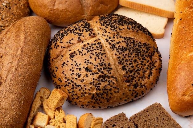 Vista do close-up de espiga de semente de papoula com baguete sem sementes e pedaços de pão e outros pães no fundo branco