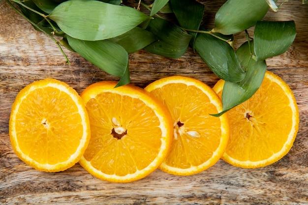Vista do close-up de fatias de laranja em fundo de madeira decorado com folhas