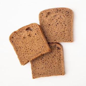 Vista do close-up de fatias de pão de centeio em fundo branco, com espaço de cópia