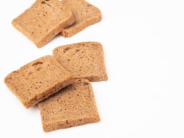 Vista do close-up de fatias de pão de centeio no lado esquerdo e fundo branco com espaço de cópia