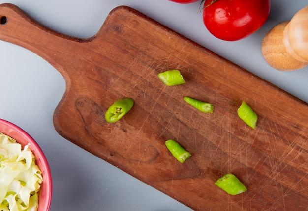 Vista do close-up de fatias de pimenta na tábua com repolho fatiado na tigela e tomate sobre fundo azul