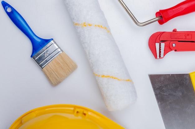 Vista do close-up de ferramentas de construção como pincel e chave de tubo de capacete de segurança de rolo e faca de vidraceiro em fundo branco