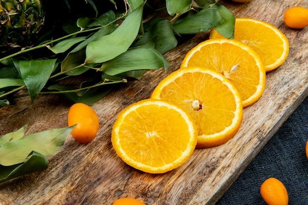 Vista do close-up de frutas cítricas como laranja e kumquat com folhas na tábua no fundo de pano de calça jeans