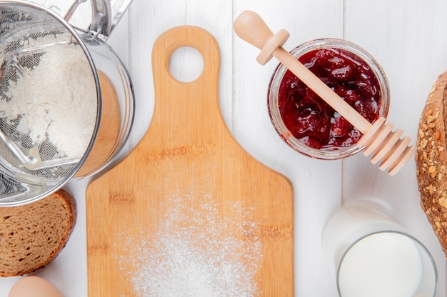 Vista do close-up de geléia de morango na fatia de farinha jar de copo de pão de centeio de leite e tábua na superfície de madeira