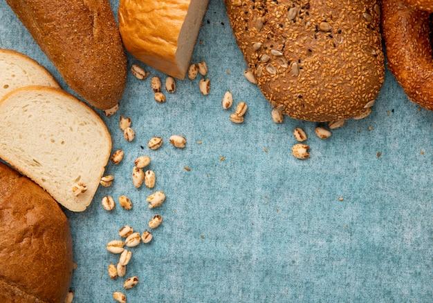 Vista do close-up de grãos com fatias de pão branco e outros tipos de pão sobre fundo azul, com espaço de cópia