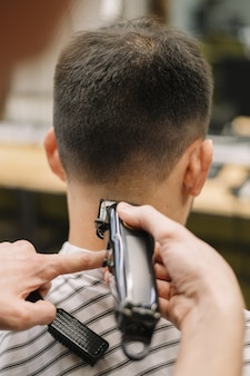 Vista do close-up de hairstilyst dando um corte de cabelo