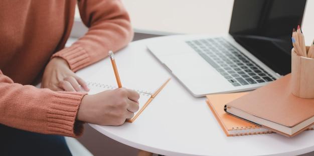Vista do close-up de jovem trabalhando em seu projeto ao elaborar sua idéia no caderno