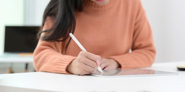 Vista do close-up de jovens mulheres trabalhando em seu projeto com tablet