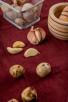 Vista do close-up de legumes como alho e mini ovo no fundo da borgonha