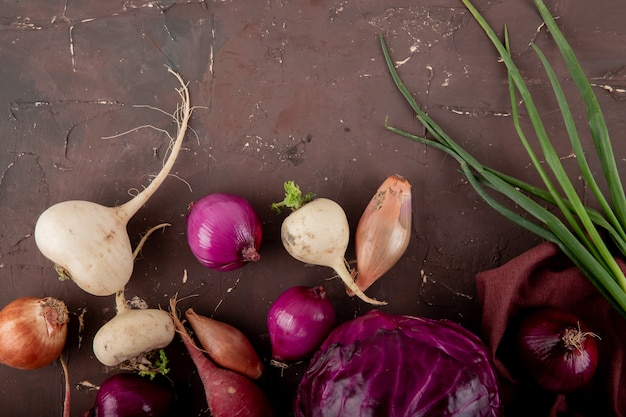 Vista do close-up de legumes como cebola de repolho roxo de cebola rabanete em fundo marrom com espaço de cópia