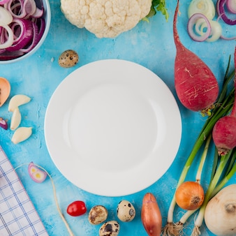 Vista do close-up de legumes como ovo de rabanete de cebola couve-flor com prato vazio no centro sobre fundo azul
