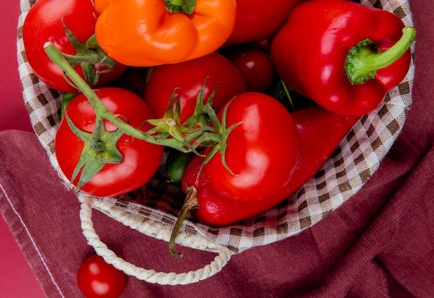 Vista do close-up de legumes como pepino tomate pimenta na cesta no pano de bordo