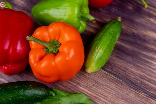 Vista do close-up de legumes como pimenta e pepino na mesa de madeira