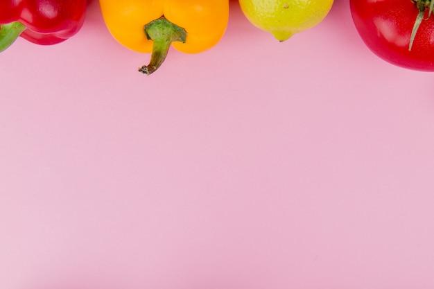 Vista do close-up de legumes como tomate pimenta com limão no fundo roxo, com espaço de cópia