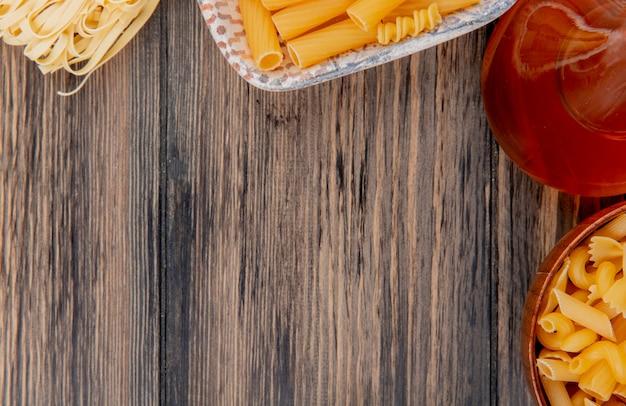 Vista do close-up de macaronis como tagliatelle ziti e outros tipos com manteiga derretida na mesa de madeira com espaço de cópia