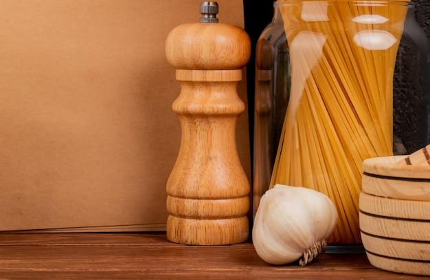 Vista do close-up de macarrão espaguete na jarra e alho com triturador de alho sal e bloco de notas na superfície de madeira e background preto com espaço de cópia