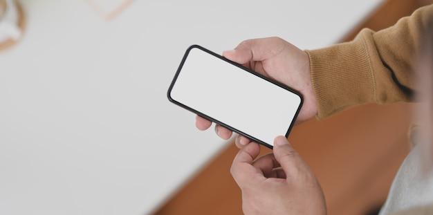 Vista do close-up de mãos de homem segurando um smartphone de tela em branco