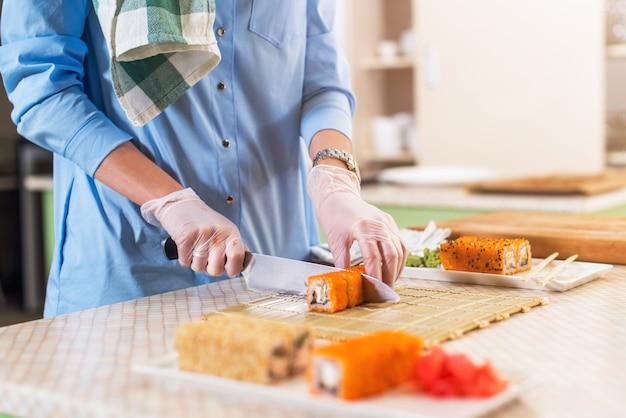 Vista do close-up de mãos femininas em luvas cozinhando rolos de sushi japonês tradicional, corte com faca na cozinha