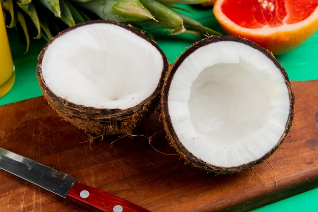 Vista do close-up de meio corte coco e faca na tábua com outras frutas cítricas sobre fundo verde