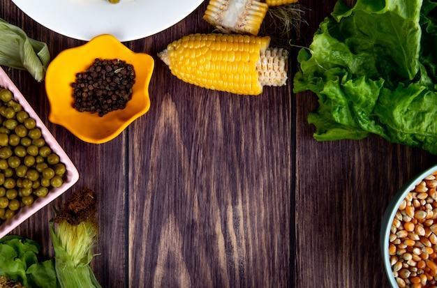 Vista do close-up de milho cortado e tigela de pimenta preta com sementes de milho alface na superfície de madeira com espaço de cópia