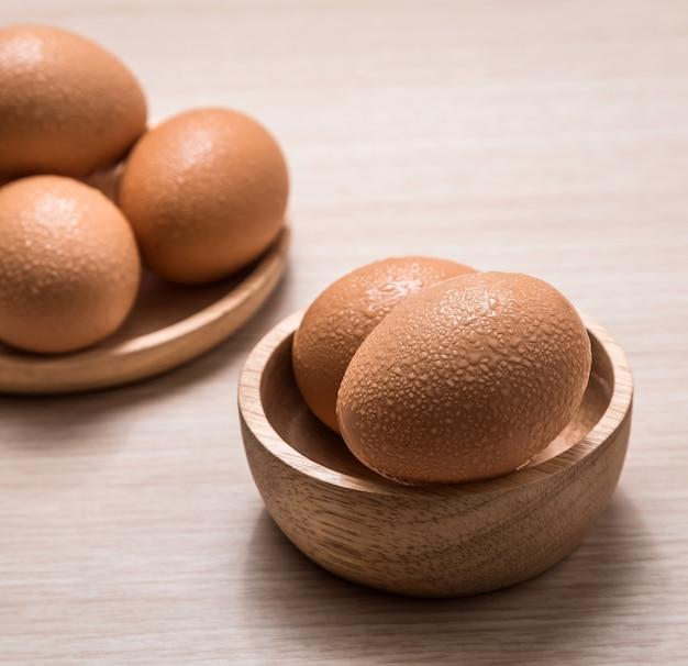 Vista do close-up de ovos de galinha no fundo da mesa de madeira