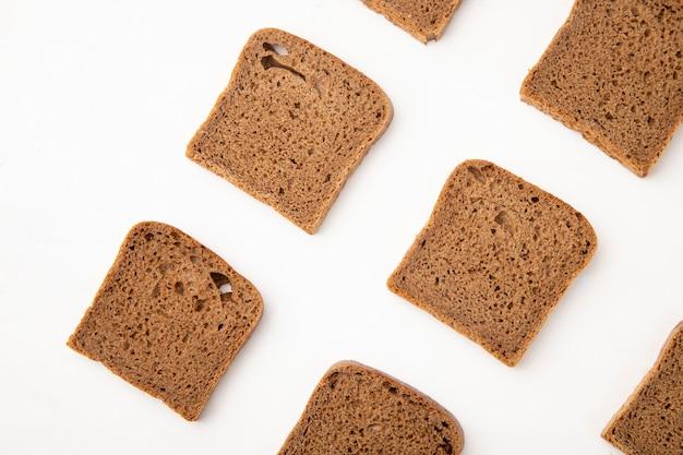 Vista do close-up de padrão de fatias de pão de centeio em fundo branco, com espaço de cópia