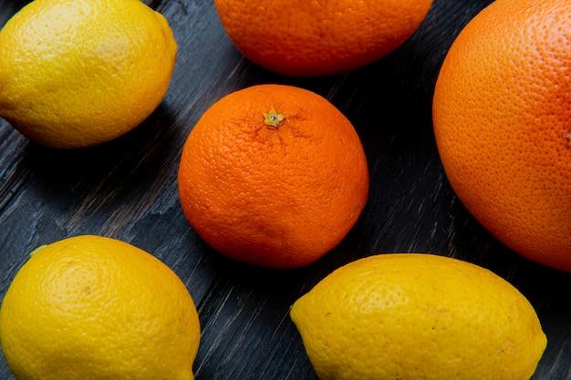 Vista do close-up de padrão de frutas cítricas como laranja tangerina limão sobre fundo de madeira