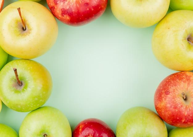 Vista do close-up de padrão de maçãs verdes e amarelas vermelhas inteiras sobre fundo verde, com espaço de cópia