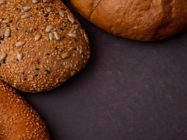Vista do close-up de pães como bagel de espiga marrom e clássico semeado em fundo marrom com espaço de cópia