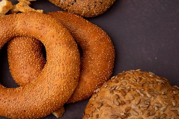 Vista do close-up de pães como bagel e espiga em fundo marrom com espaço de cópia