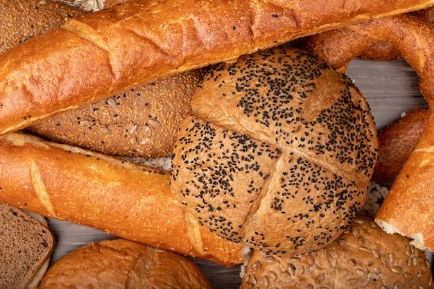 Vista do close-up de pães como sementes de papoila baguete bagel e outros sobre fundo de madeira