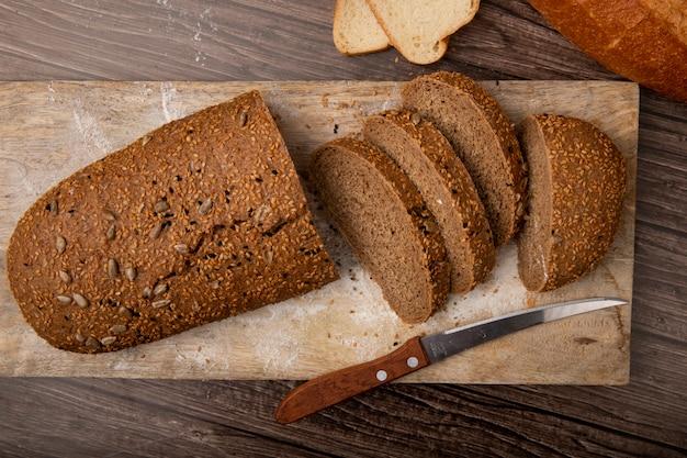 Vista do close-up de pão fatiado e cortado com faca na tábua sobre fundo de madeira