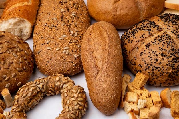 Vista do close-up de pedaços de pão e baguete sem sementes com espigas de pão no fundo branco