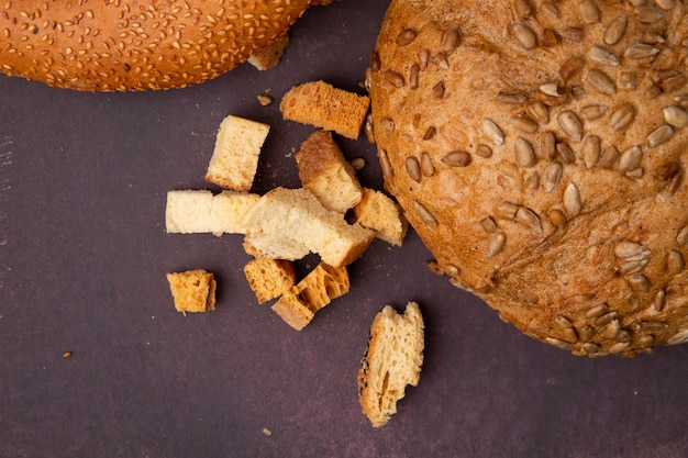 Vista do close-up de pedaços de pão e espiga semeada marrom no fundo maron com espaço de cópia