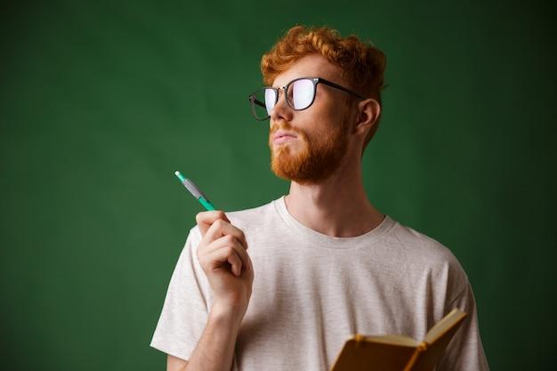 Vista do close-up de pensar jovem barbudo em camiseta branca, segurando um caderno e uma caneta
