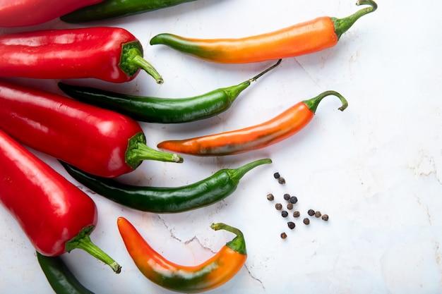 Vista do close-up de pimentas e temperos de pimenta no fundo branco, com espaço de cópia