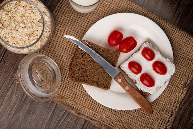Vista do close-up de placa com fatias de pão de centeio manchada com queijo cottage e tomate e faca com flocos de aveia em fundo de madeira