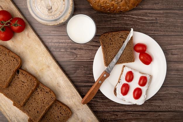 Vista do close-up de prato com fatias de pão de centeio e tomates e faca com flocos de aveia com leite no fundo de madeira