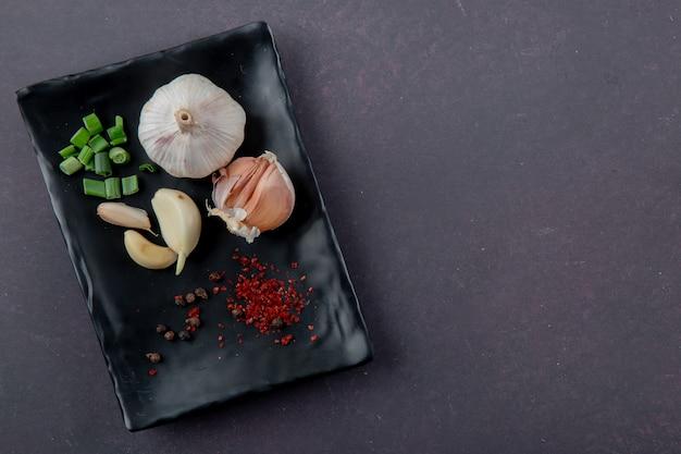 Vista do close-up de prato de legumes como alho cortado cebolinha com especiarias em fundo marrom com espaço de cópia