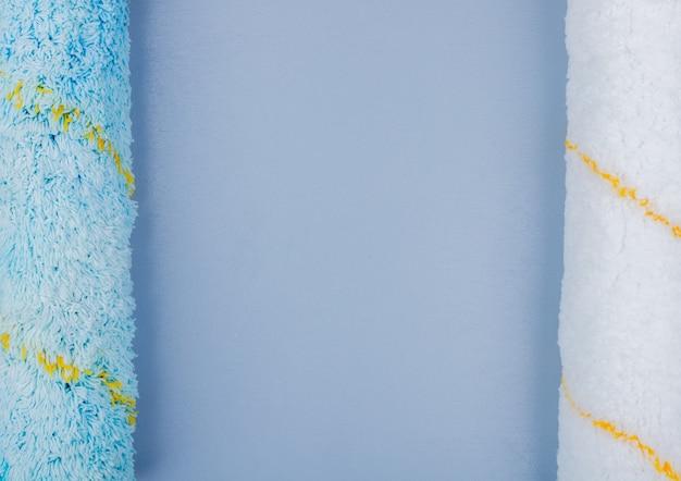 Vista do close-up de rolos de pintura sobre fundo cinzento, com espaço de cópia
