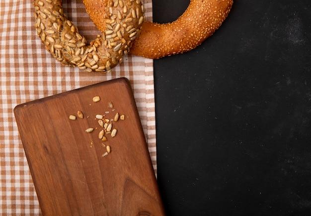 Vista do close-up de sementes de girassol na tábua e bagels no pano em fundo preto, com espaço de cópia