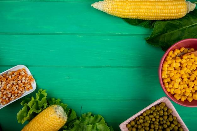 Vista do close-up de sementes de milho em colher com espinafre de alface calos sobre fundo verde, com espaço de cópia