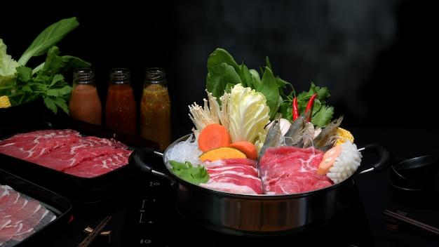 Vista do close-up de shabu shabu em panela quente com fundo preto, carne fatiada fresca, frutos do mar e legumes