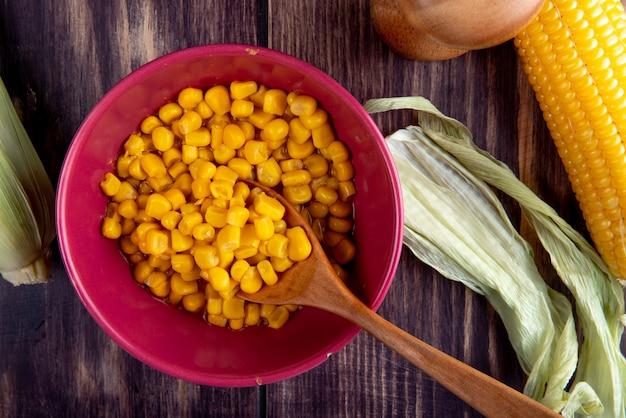 Vista do close-up de tigela cheia de sementes de milho com colher de pau e milho com casca na mesa de madeira