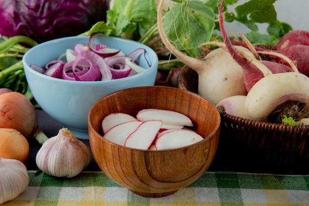 Vista do close-up de tigelas e cesta de legumes como alho de rabanete de cebola na superfície do pano