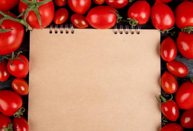 Vista do close-up de tomates em torno do bloco de notas na mesa de madeira com espaço de cópia