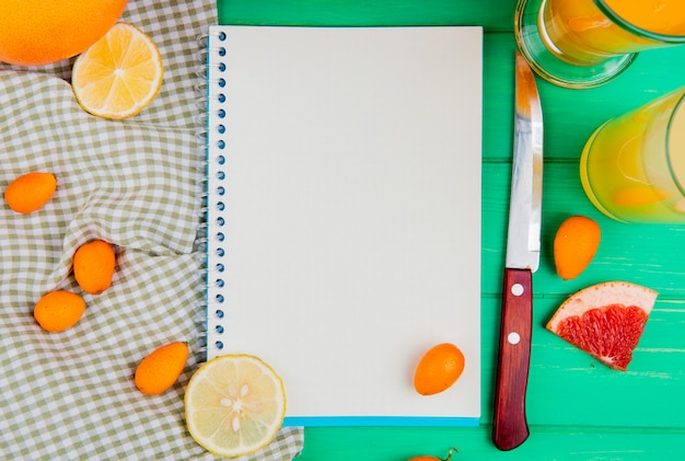 Vista do close-up do bloco de notas com faca de laranja toranja kumquat e sucos ao redor sobre fundo verde, com espaço de cópia