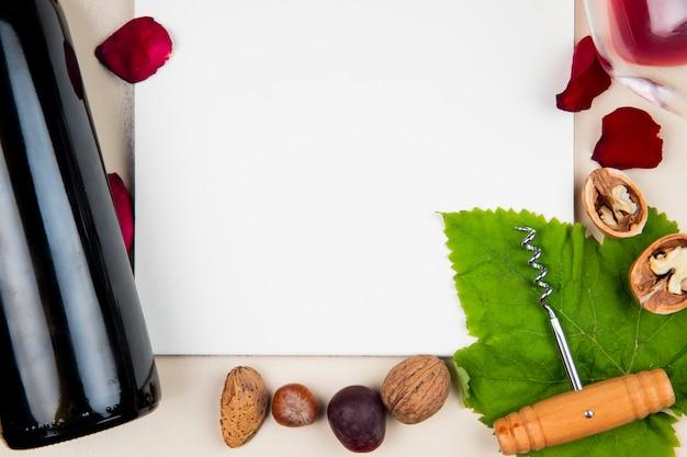 Vista do close-up do bloco de notas com garrafa de saca-rolhas de nozes de vinho tinto e pétalas de amêndoa e flor ao redor em branco com espaço de cópia