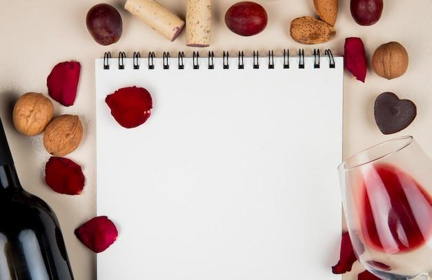 Vista do close-up do bloco de notas com vidro e garrafa de rolhas de nozes de vinho tinto e pétalas de flores ao redor em branco com espaço de cópia